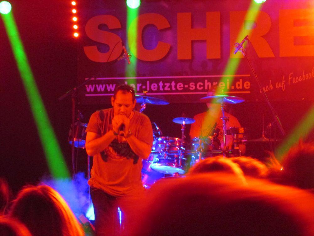 Sänger Claus Schäfer steht im Licht.