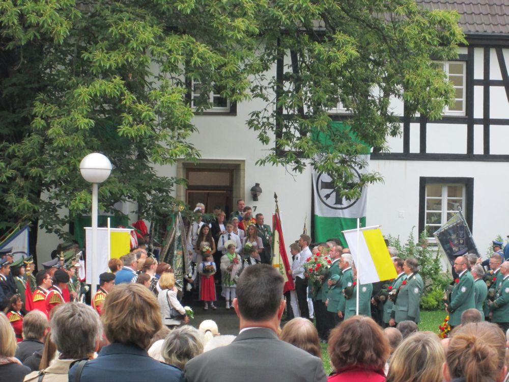 Vor der Tür des Pfarrhauses stehen die neuen und alten Königspaare der Schützen und Jungschützen.