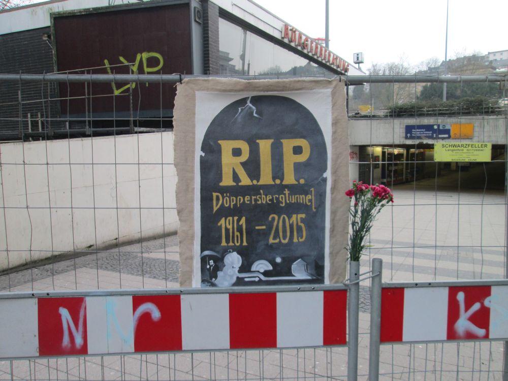 """Plakat """"R.I.P. Döppersbergtunnel 1961-2015"""" und ein Blumenstrauß am Bauzaun."""