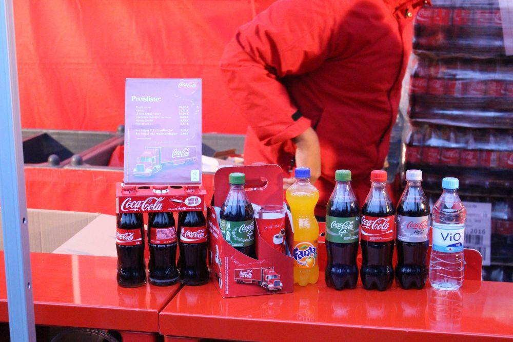 Verkaufsstand mit den verschiedenen Cola-Produkten (von rechts nach links): ViO, Cola Light, Coca-Cola, Coca-Cola life, Fanta, Viererpack mit Weihnachtsglas (2,95 Euro plus Pfand) und Sechserpack mit Coca-Cola Glasflaschen (3,25 Euro plus Pfand).