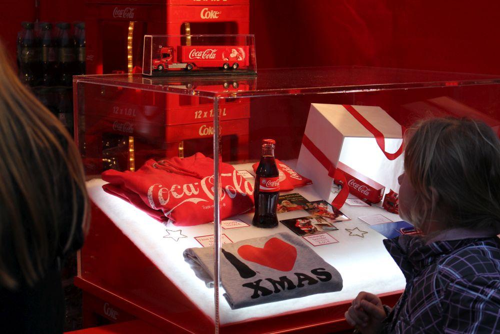 """Coca-Cola-Merchandising: Oben ein Modelltruck (19 Euro), links Hoody (15 Euro) und """"I love XMAS""""-T-Shirt (10 Euro), rechts Handy-Socke (4,50 Euro), nochmal der Modelltruck, kleine Nostalgieschilder (6 Euro/3 Stück) und Poster (2,50/DIN A2)."""