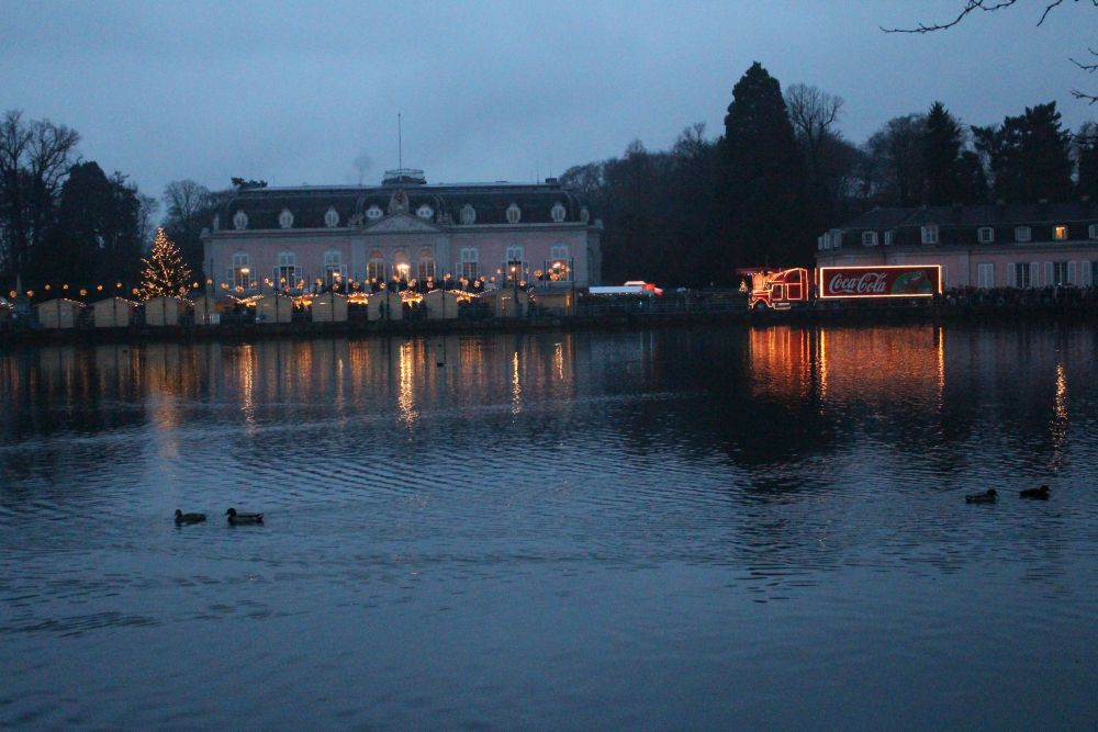 Blick vom Ufer gegenüber: Links die Weihnachtsbuden mit dem Schloss Benrath im Hintergrund, auf der rechten Seite der beleuchtete Coca-Cola Weihnachtstruck.